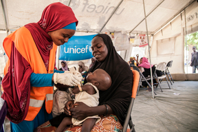 On 17th November 2016, UNICEF Nutrition Officer, Aishat Abdullahi, assesses 7 month old Umara Bukar for malnutrition at a UNICEF supported health clinic at Muna Garage IDP camp, Maiduguri, Borno State, northeast Nigeria as Umara's mother (in black) looks on. 20 days ago Umara weighed just 4.2kg when he first arrived at the health clinic run in partnership with the Nigerian government. He now weighs 5.1kg. To date, over 117,00 children with severe acute malnutrition (SAM) in northeast Nigeria have been admitted to therapeutic feeding programmes run by UNICEF and partners.