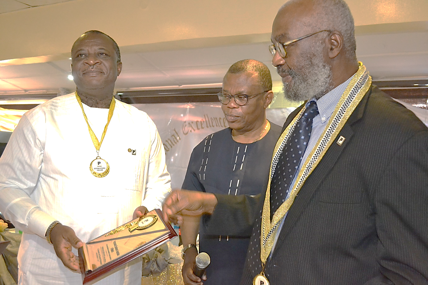 L-R: Pharm. Ike Ugwu, chief executive officer, Pharmacare Support Group receiving a Fellowship award plaque from Sir Ifeanyi Atueyi, PEFON Board of Trustees member while Engr. Ibikunle Oguntayo, representative of Prince Juli Adelusi-Adeluyi, looks on